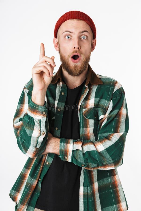 Imagen del sombrero del individuo barbudo emocionado y de la camisa de tela escocesa que llevan que señalan el finger hacia arrib imagen de archivo libre de regalías