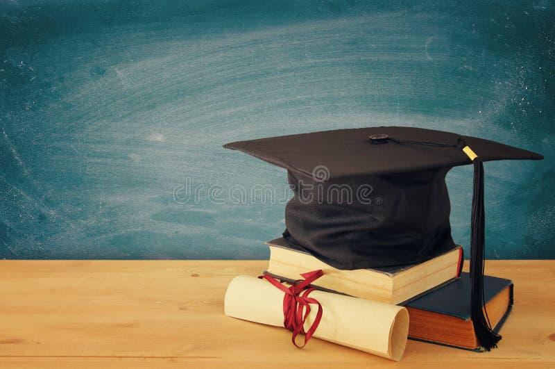 Imagen del sombrero negro de la graduación sobre los libros viejos al lado de la graduación en el escritorio de madera Educación  imagen de archivo