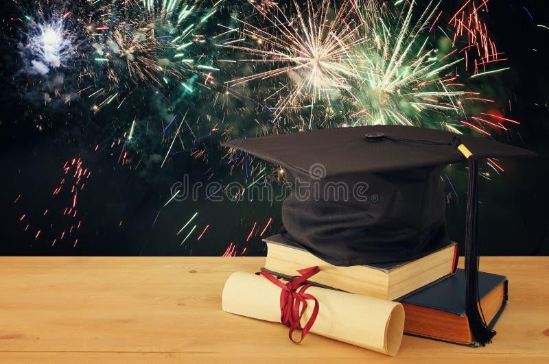 Imagen del sombrero negro de la graduación sobre los libros viejos al lado de la graduación en el escritorio de madera Educación  fotografía de archivo