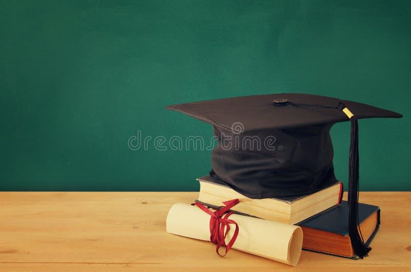 Imagen del sombrero negro de la graduación sobre los libros viejos al lado de la graduación en el escritorio de madera Educación  fotografía de archivo libre de regalías