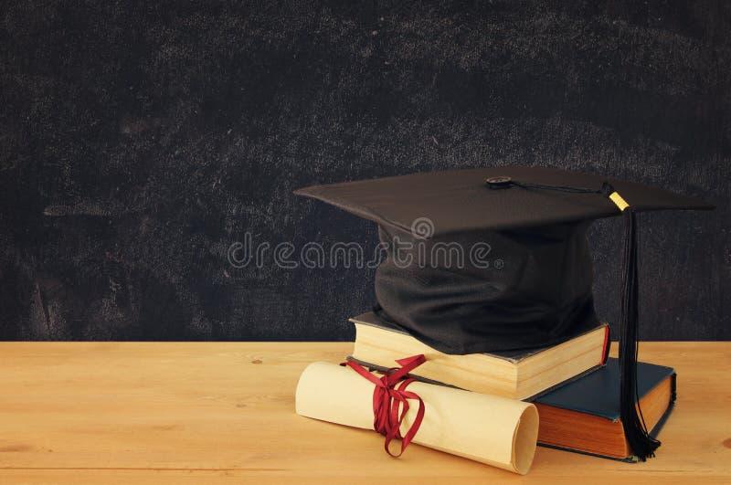 Imagen del sombrero negro de la graduación sobre los libros viejos al lado de la graduación en el escritorio de madera Educación  imagenes de archivo