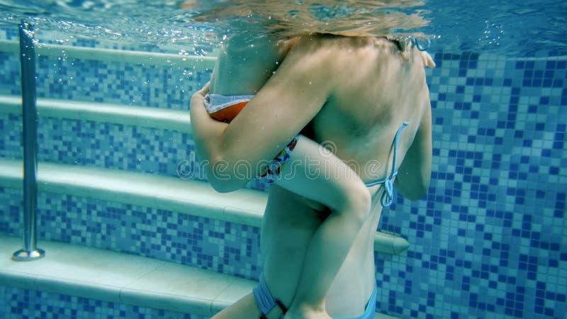 Imagen del submarino del primer de poco ni?o peque?o con la madre joven que se relaja en piscina foto de archivo libre de regalías