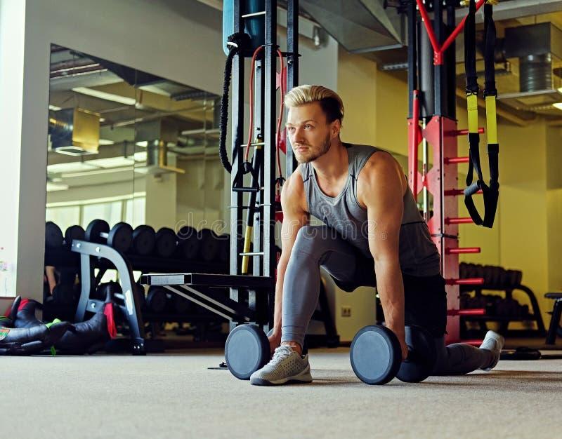 Imagen del varón atlético del cuerpo completo que hace posiciones en cuclillas con pesas de gimnasia en un club del gimnasio fotografía de archivo