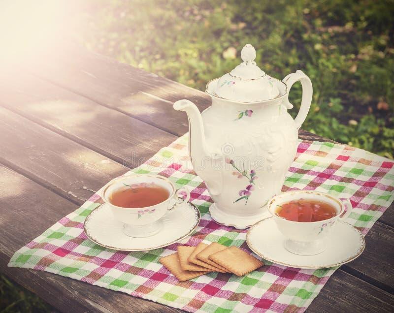 Imagen del vintage de las tazas de té y de la tetera en t de madera imagen de archivo libre de regalías