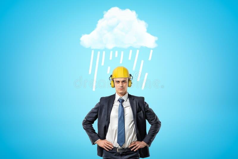 Imagen delantera de la cosecha del hombre de negocios en casco amarillo con los protectores contra el ruido, colocándose con las  imagenes de archivo