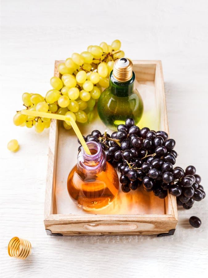 Imagen desde arriba de la bandeja de madera con las uvas verdes y negras, dos botellas de jugo imagen de archivo libre de regalías