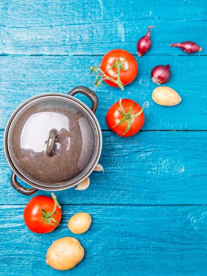 Imagen desde arriba del pote del hierro, tomate, patata, cebolla en fondo de madera azul fotografía de archivo