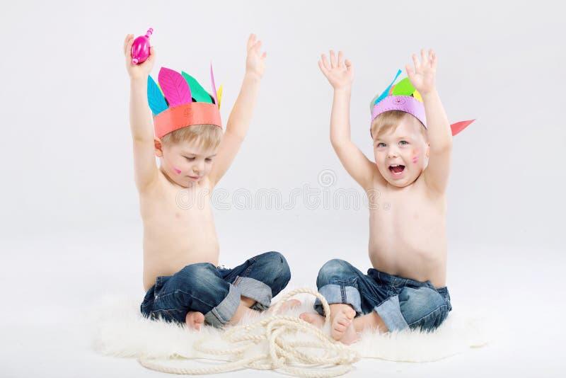 Imagen divertida de dos muchachos que juegan a indios foto de archivo