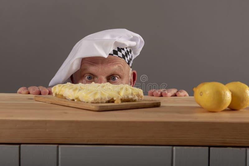 Imagen divertida de un cocinero maduro que mira una torta del limón fotografía de archivo