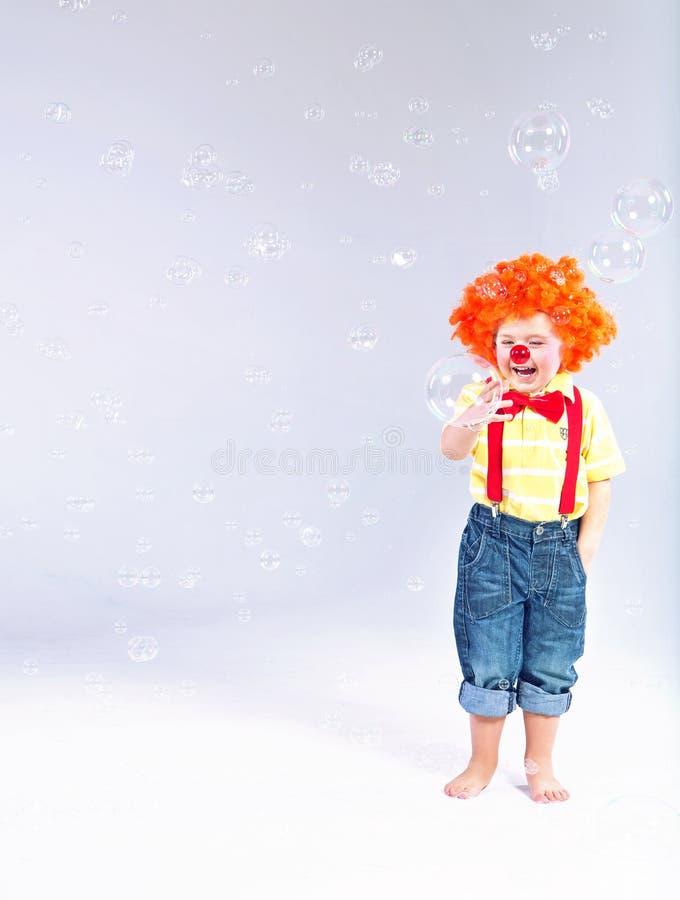 Imagen divertida del pequeño payaso que hace burbujas de jabón enormes imágenes de archivo libres de regalías