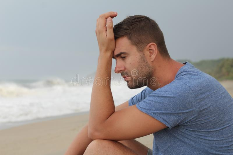Imagen dramática del hombre pensativo en la playa imagenes de archivo
