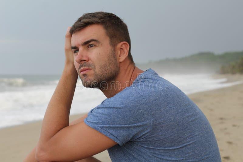 Imagen dramática del hombre pensativo en la playa fotografía de archivo