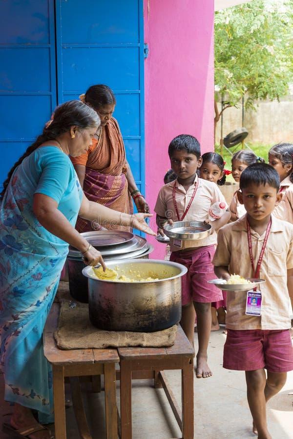 Imagen editorial documental No identificado womaen a los niños del servicio para el almuerzo en la cantina al aire libre foto de archivo libre de regalías