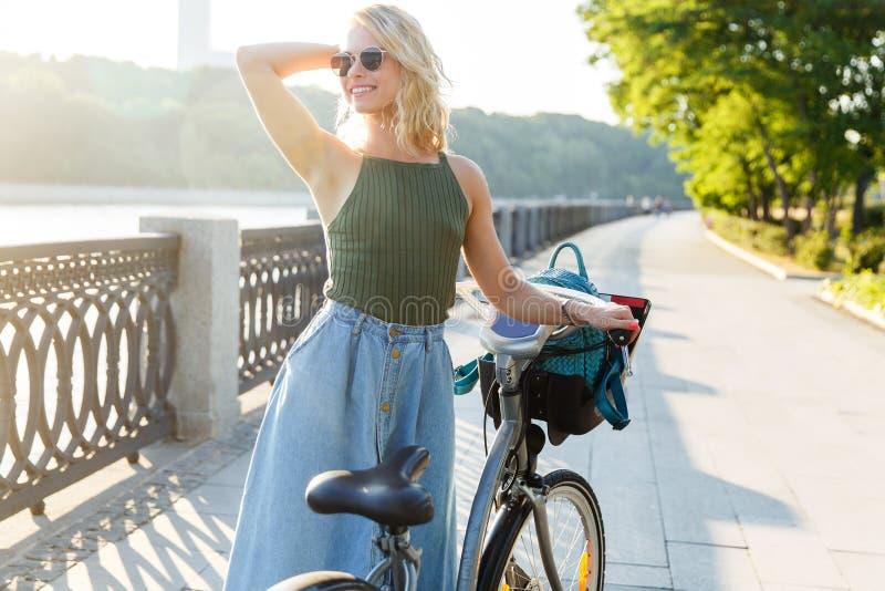 Imagen en del lado de mirada rubio rizado en la situación de la falda del dril de algodón al lado de la bici en el puente en ciud imágenes de archivo libres de regalías