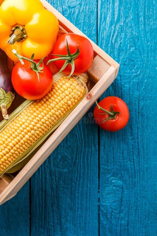 Imagen encima de la caja de madera con el maíz, pimienta, tomate fotos de archivo libres de regalías