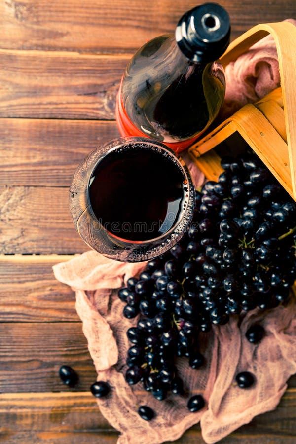 Imagen encima de la copa de vino con el vino, uvas de la cesta negra, de madera, paño imagenes de archivo