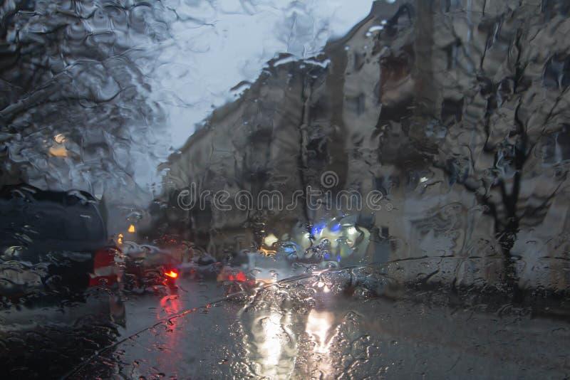Imagen enfocada del De de la lluvia que baja en el camino, mirando hacia fuera la ventana Silueta borrosa del coche imagen de archivo libre de regalías