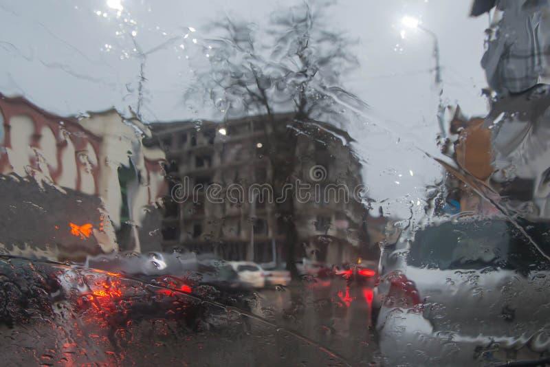 Imagen enfocada del De de la lluvia que baja en el camino, mirando hacia fuera la ventana Silueta borrosa del coche foto de archivo