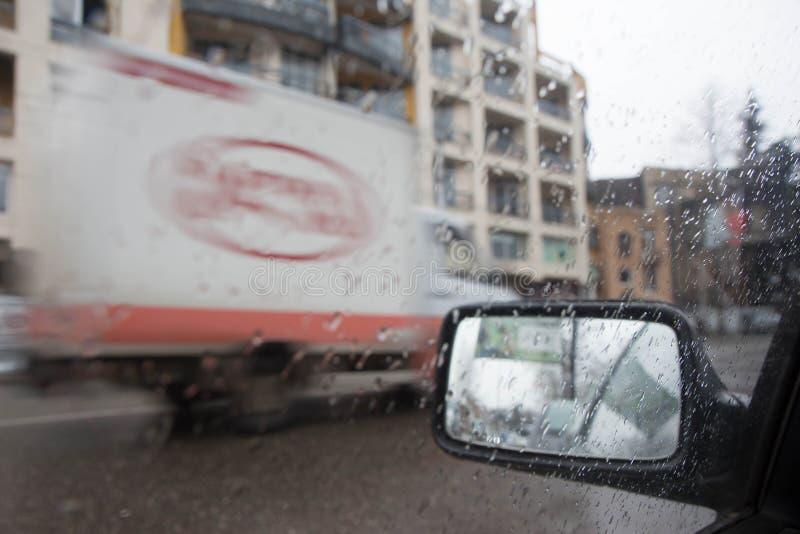 Imagen enfocada del De de la lluvia que baja en el camino, mirando hacia fuera la ventana Silueta borrosa del coche fotos de archivo