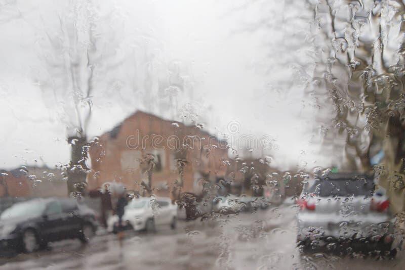 Imagen enfocada del De de la lluvia que baja en el camino, mirando hacia fuera la ventana Silueta borrosa del coche fotos de archivo libres de regalías
