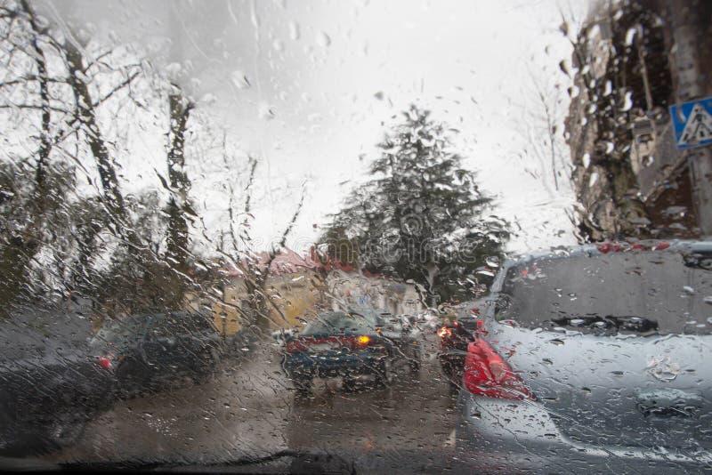 Imagen enfocada del De de la lluvia que baja en el camino, mirando hacia fuera la ventana Silueta borrosa del coche imágenes de archivo libres de regalías