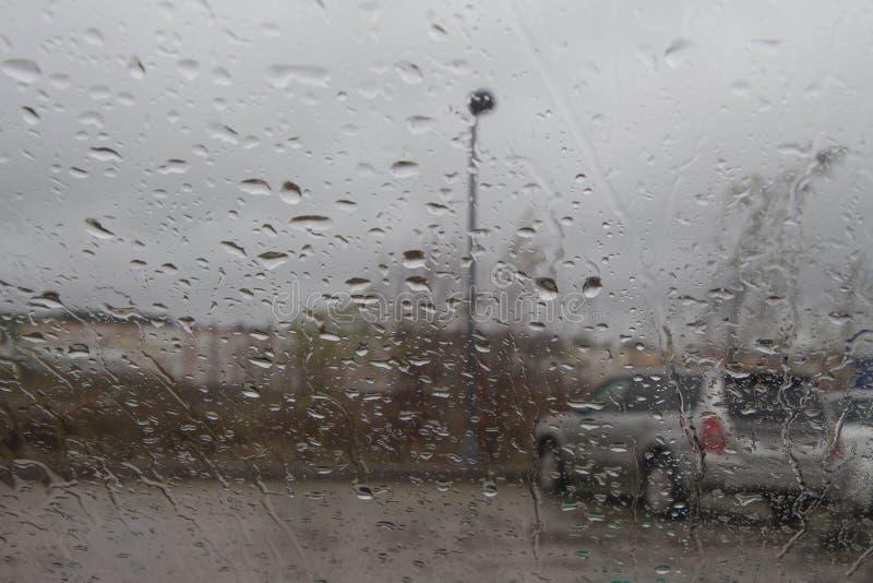 Imagen enfocada del De de la lluvia que baja en el camino, mirando hacia fuera la ventana Silueta borrosa del coche fotografía de archivo