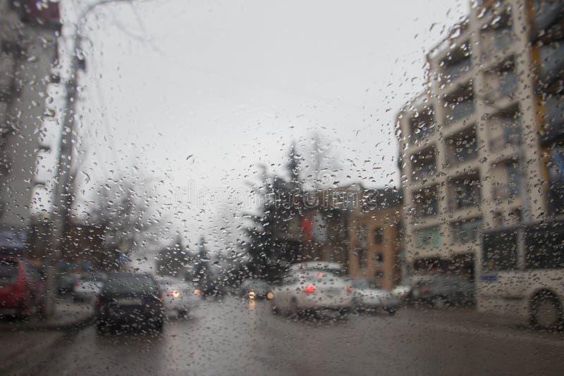 Imagen enfocada del De de la lluvia que baja en el camino, mirando hacia fuera la ventana Silueta borrosa del coche Gotas de lluv fotografía de archivo libre de regalías