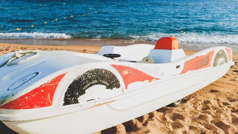 Imagen entonada del barco viejo del pedal del catamarán en la playa arenosa contra ondas del mar tranquilo fotografía de archivo