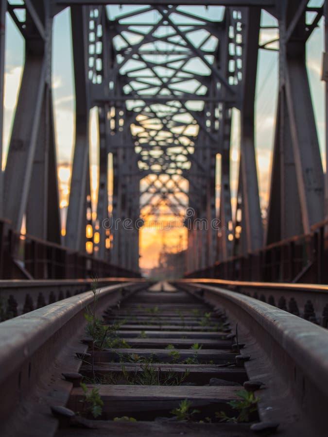 Imagen entonada del ferrocarril con los durmientes y del puente del carril en un fondo de la puesta del sol multicolora fotografía de archivo libre de regalías