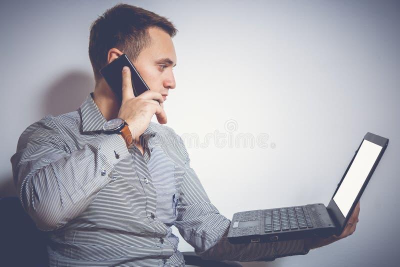 Imagen entonada Hombre de negocios joven con el ordenador portátil y el teléfono Él mira la pantalla y habla en el móvil foto de archivo