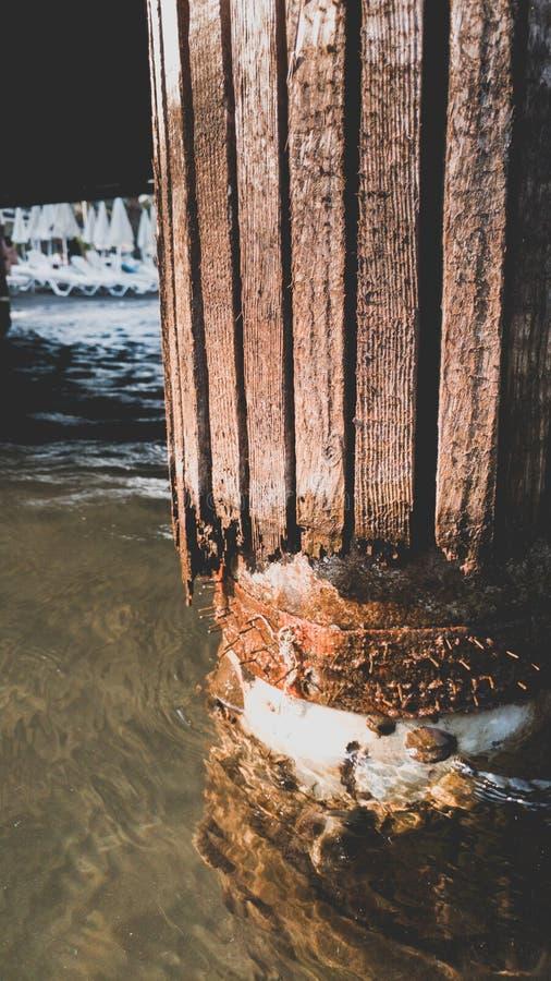 Imagen entonada primer de destructing columnas de madera del embarcadero viejo en la orilla de mar imagen de archivo libre de regalías