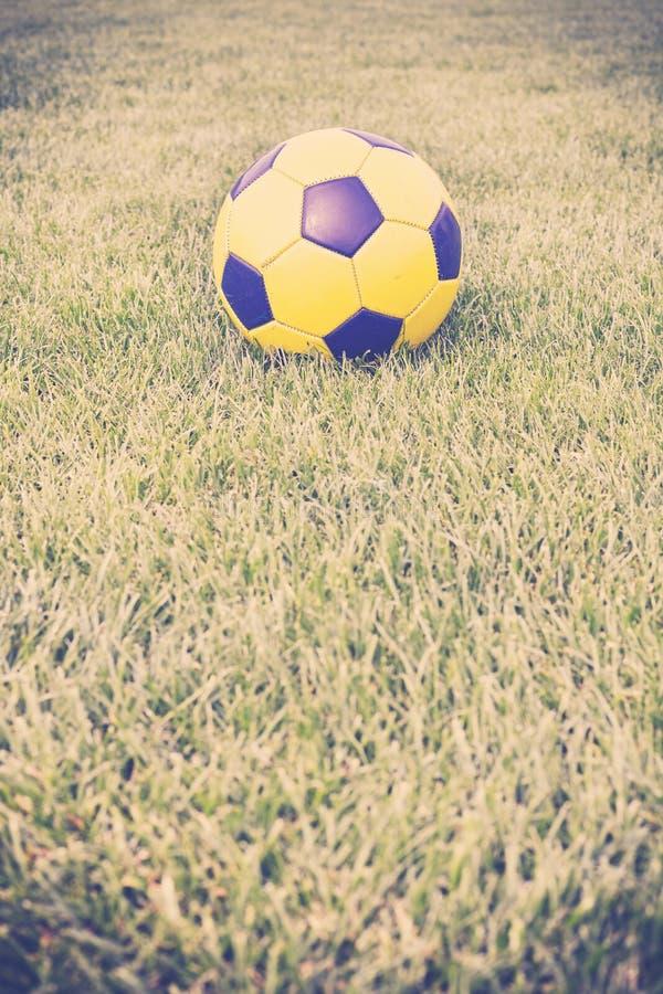 Imagen entonada retra de un balón de fútbol en hierba foto de archivo