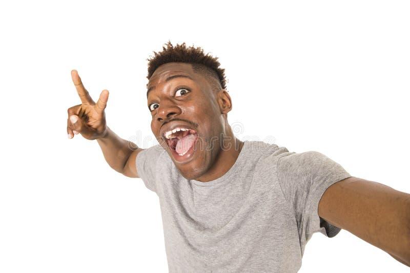 Imagen feliz sonriente del autorretrato del selfie del hombre que toma afroamericano joven con el teléfono móvil imagenes de archivo