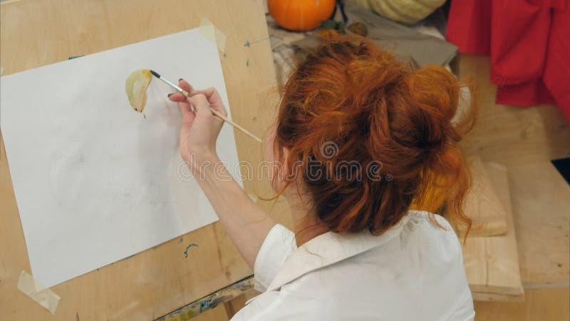 Imagen femenina joven de la acuarela de la pintura del artista en estudio foto de archivo