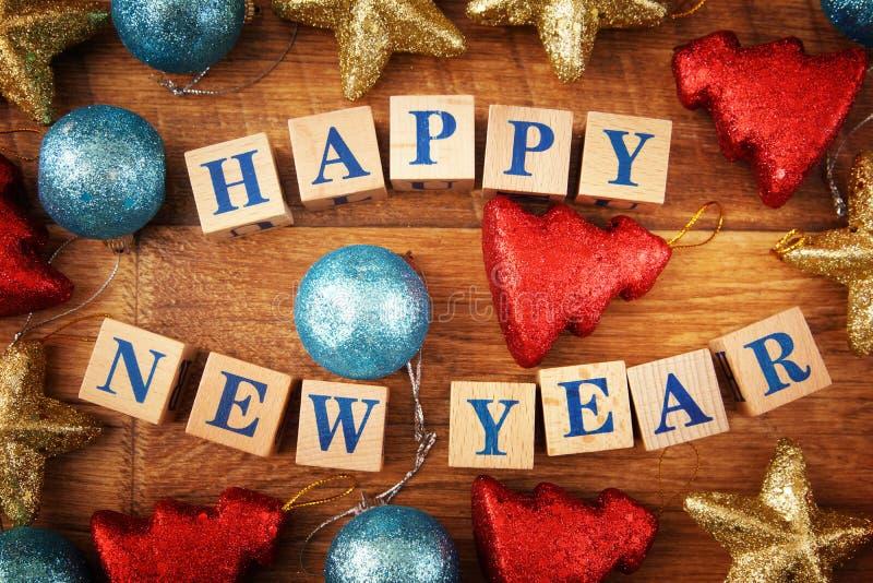 Imagen festiva del Año Nuevo con un texto en los cubos de madera y los juguetes coloridos brillantes fotografía de archivo