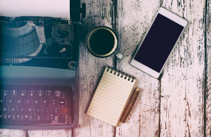 Imagen filtrada retra de la máquina de escribir del vintage, del cuaderno en blanco, de la taza de café y del smartphone en la ta imágenes de archivo libres de regalías