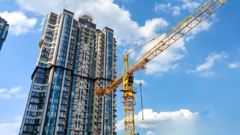 Imagen hermosa de la alta grúa constructiva amarilla en emplazamiento de la obra contra el alto edificio moderno hecho de concret imagenes de archivo