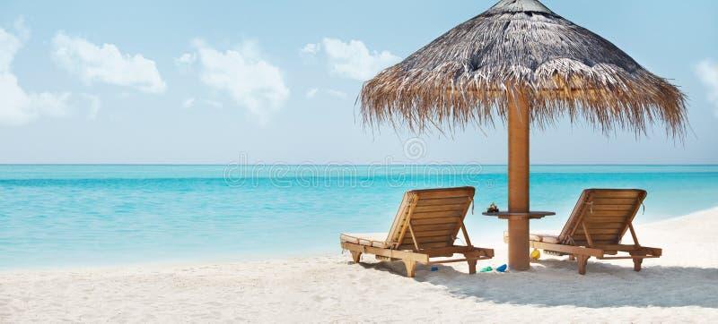 Imagen hermosa de la playa y de la silla de reclinación imagen de archivo libre de regalías