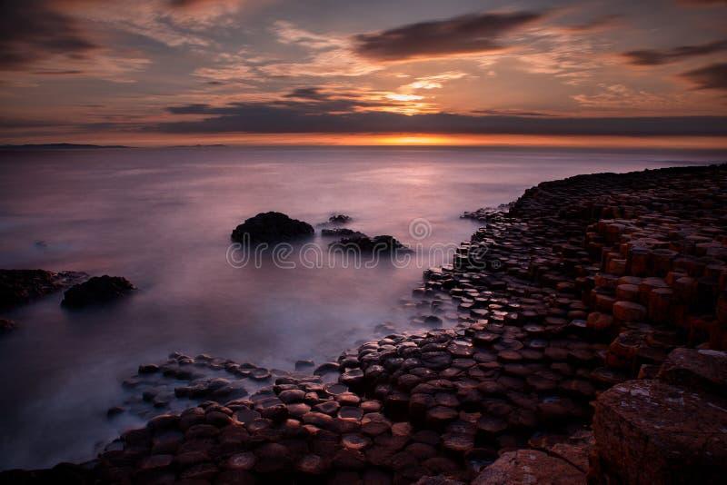 Imagen hermosa de la puesta del sol sobre horizonte de mar, y formaciones de roca volcánica únicas en el terraplén de Giants, Nor imagenes de archivo