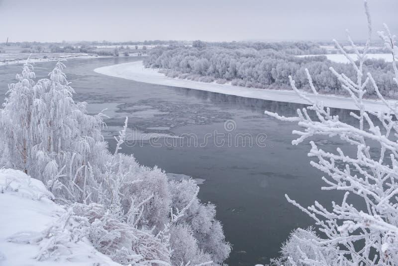 Imagen hermosa del invierno landscape río ancho con los árboles plateados nevados en los bancos imagenes de archivo
