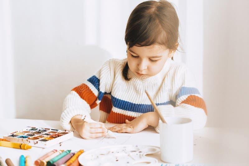 Imagen horizontal de los lápices de pintura del withoil de la niña linda, sentándose en el escritorio blanco en casa Dibujo prees imagen de archivo