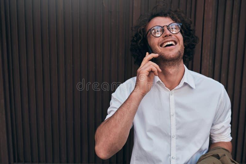 Imagen horizontal del hombre de negocios hermoso feliz que presenta contra la pared del edificio mientras que se coloca al aire l foto de archivo libre de regalías