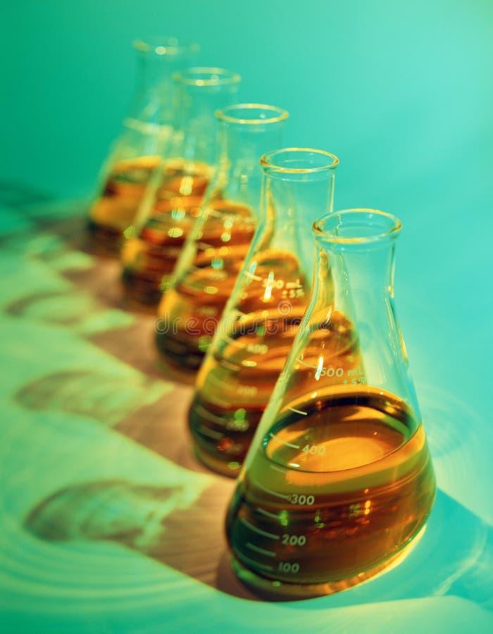 Imagen ilustrativa del foco selectivo de frascos químicos en verde foto de archivo