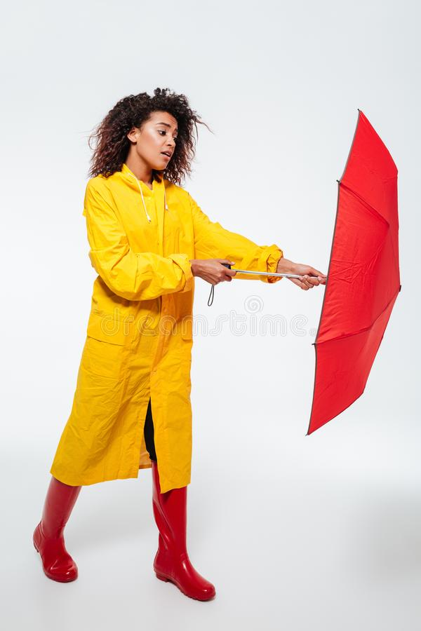 Imagen integral de la mujer africana confusa en paraguas de la abertura del impermeable fotografía de archivo libre de regalías