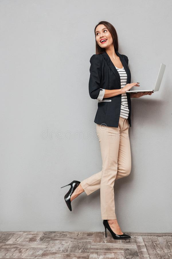 Imagen integral de la mujer de negocios feliz que sostiene el ordenador portátil fotografía de archivo