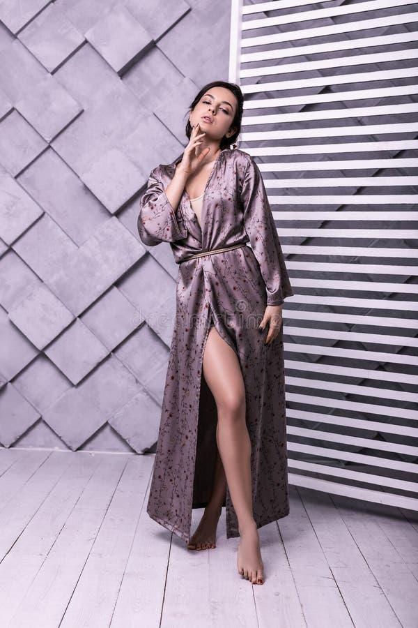 Imagen integral de posturing modelo en la ropa de seda blanda de la lila imagenes de archivo