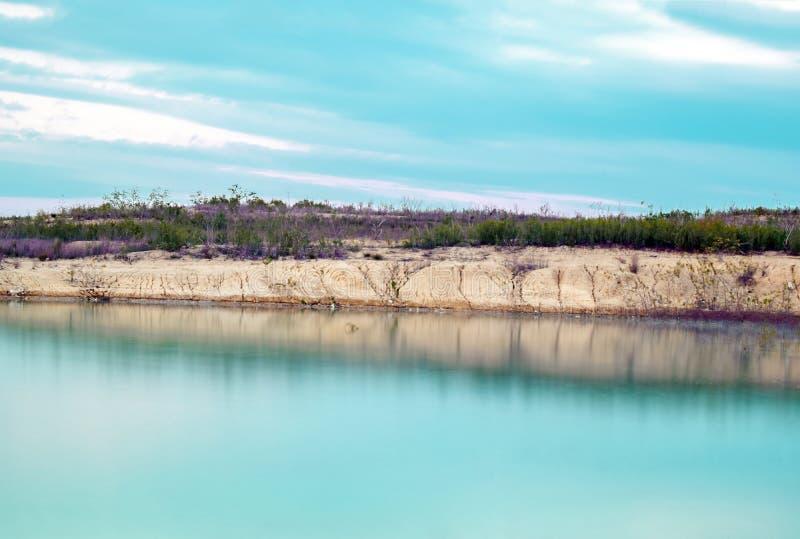 Imagen larga de la exposición del agua lechosa del lago contra en puesta del sol imagenes de archivo