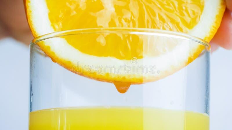 Imagen macra de la mano que exprime el zumo de naranja en vidrio imagen de archivo libre de regalías