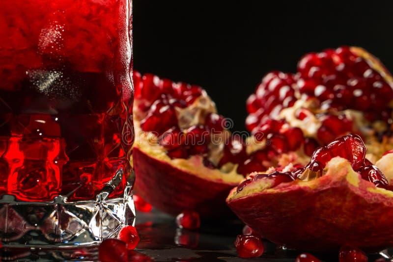 Imagen macra de un granate jugoso rojo Cóctel alcohólico amargo sano de la baya y de la granada en un fondo negro Verano fotografía de archivo