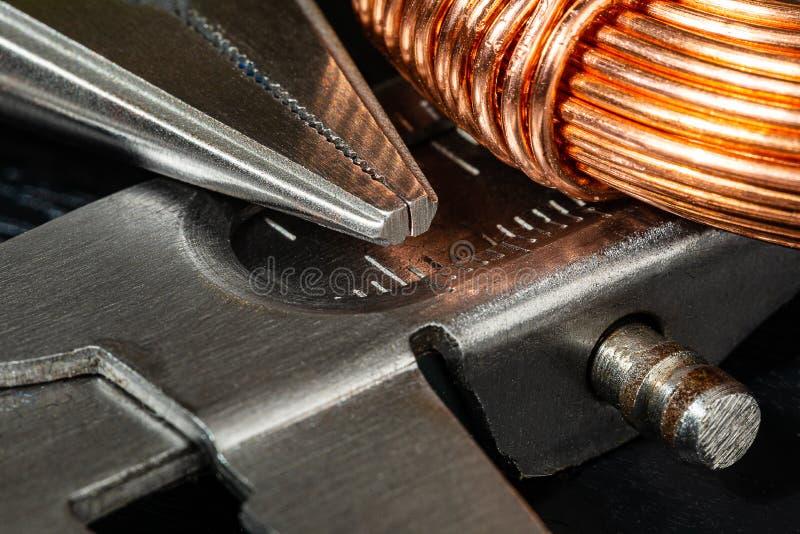 Imagen macra de una bobina del alambre de cobre y de un par de alicates de punta de aguja con el calibrador de un carpintero foto de archivo libre de regalías